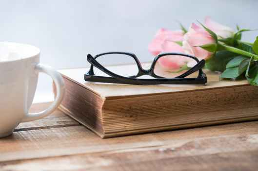 eyeglasses on book beside pink rose on cup