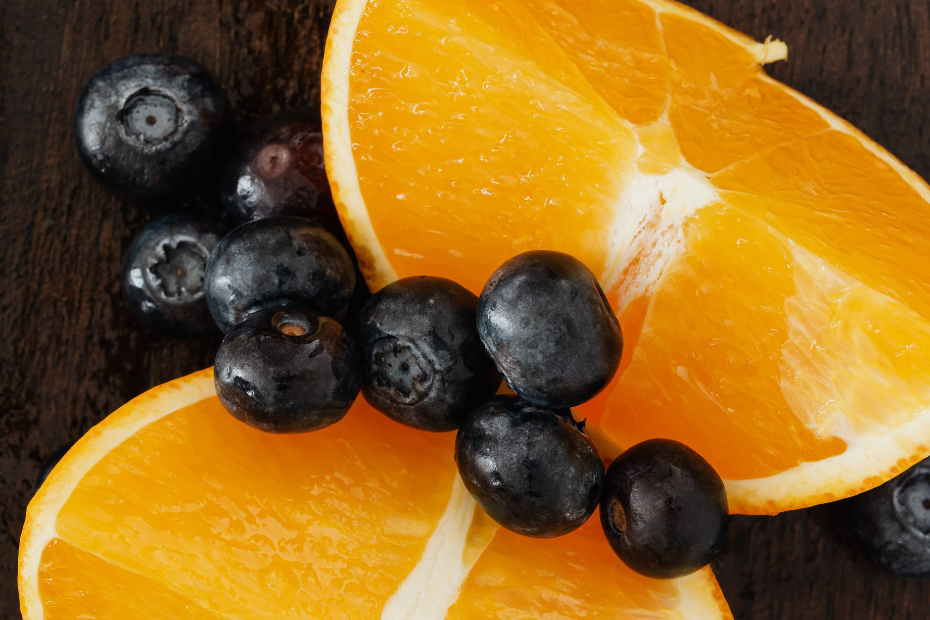 closeup of delicious blueberries placed on juicy oranges on wooden table