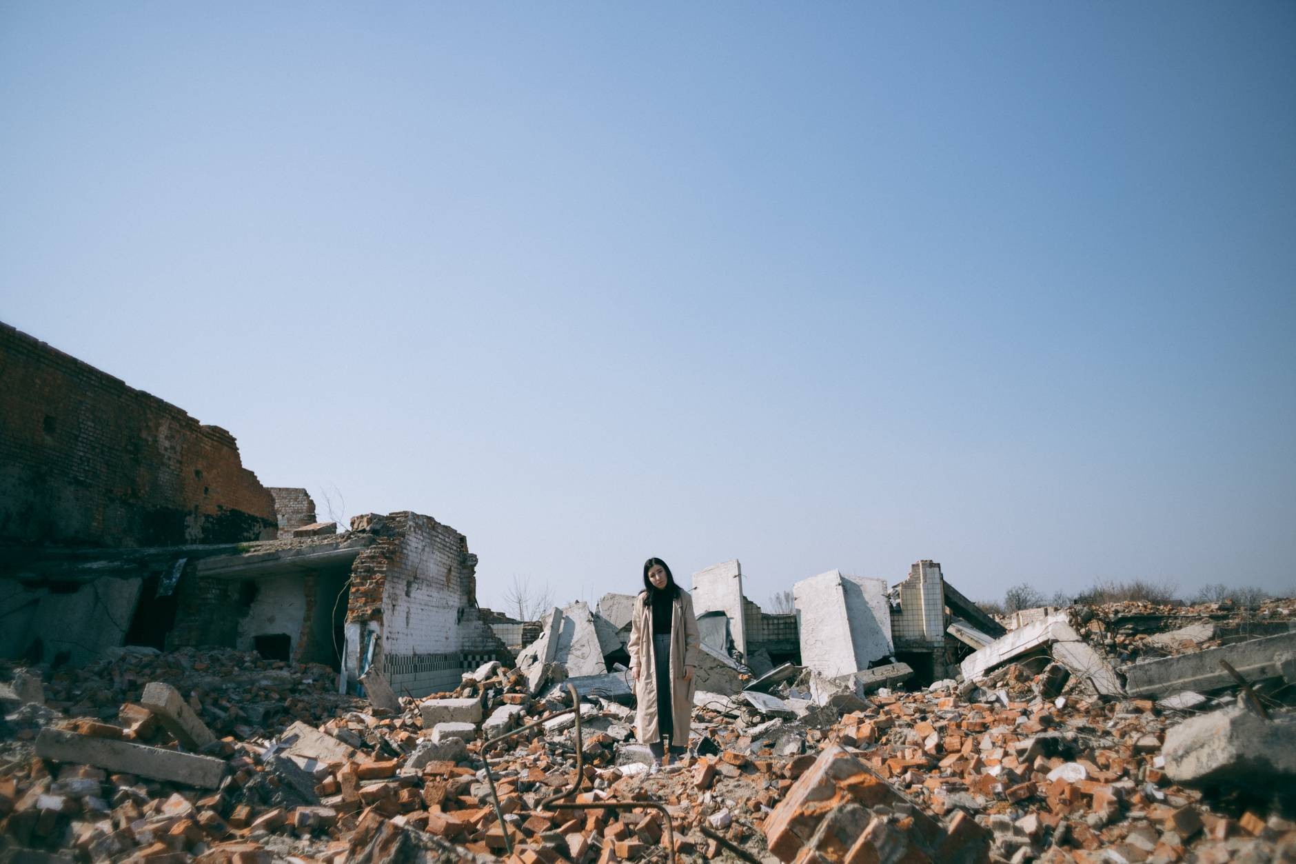 woman standing on ruins of a building