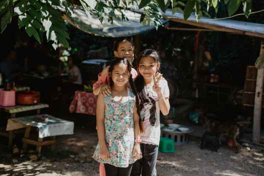 cheerful little asian kids spending time on street