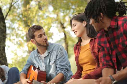 male with guitar singing with friends