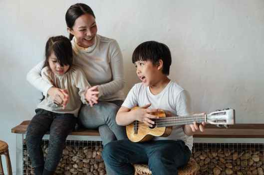 ethnic boy playing ukulele while sitting with mother and sister