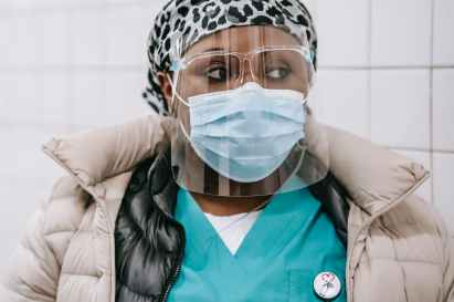 crop black nurse in outerwear mask and face shield