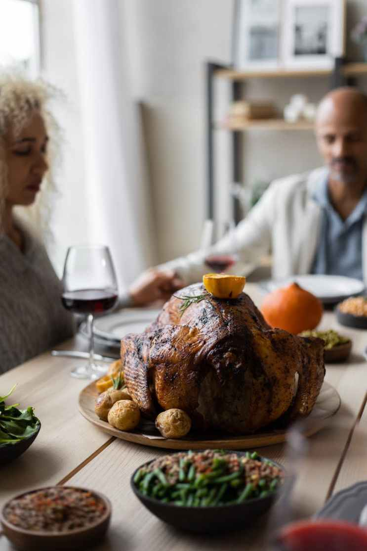 crop multiethnic friends praying at table on thanksgiving